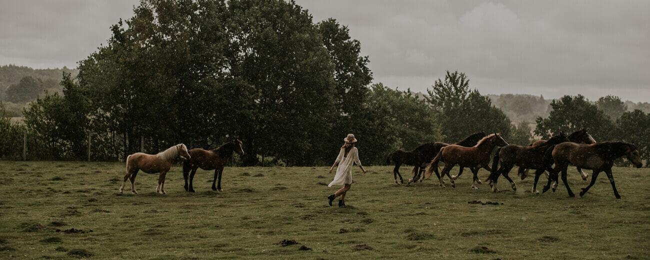 Ein Mädchen in einem Sommerspitzenkleid mit Pferden